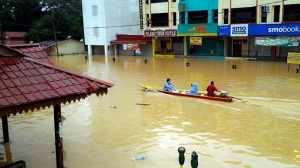 In this Dec. 24, 2014 photo, residents using a boat pass by flooded shops in Kuala Krai, Kelantan state, Malaysia. The worst floods in the country in decades that have killed people and displaced more than 100,000. (AP Photo)